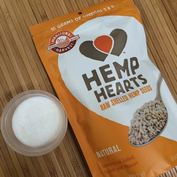Manitoba Hemp Hearts next to a small cup of freshly blended hemp milk.